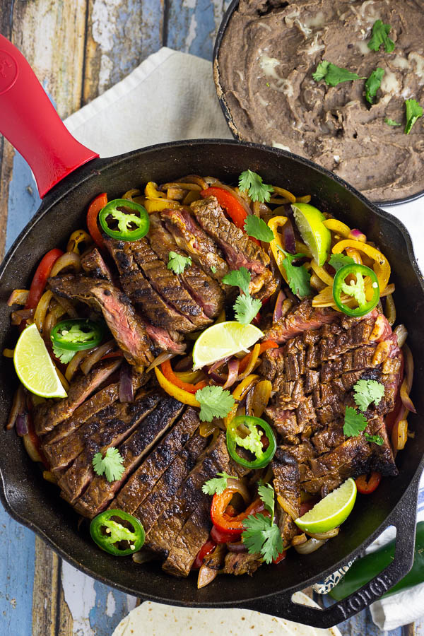 Steak fajitas in  a black cast iron skillet with red and yellow bell peppers and fresh slices of jalapenos and lime.