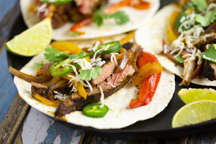 Close up of a steak fajita on a flour tortilla sitting on a black place with lime wedges