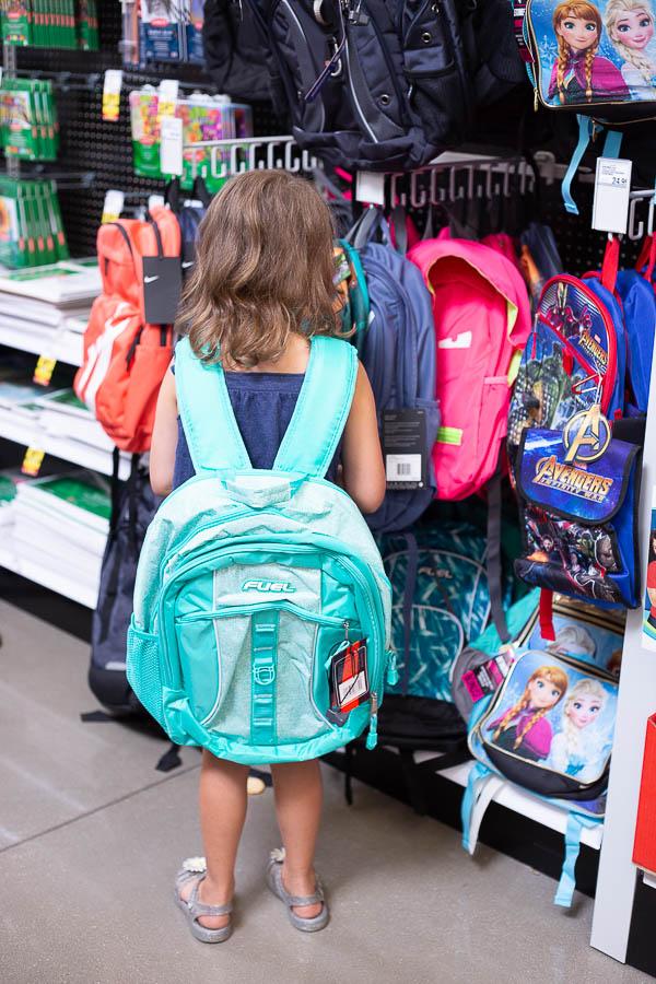 Little girl facing backward wearing an aqua backpack