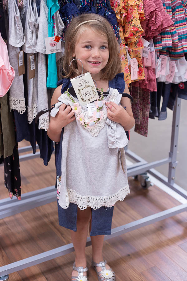 Little girl holding gray shirt in front of a rack of clothes at a store