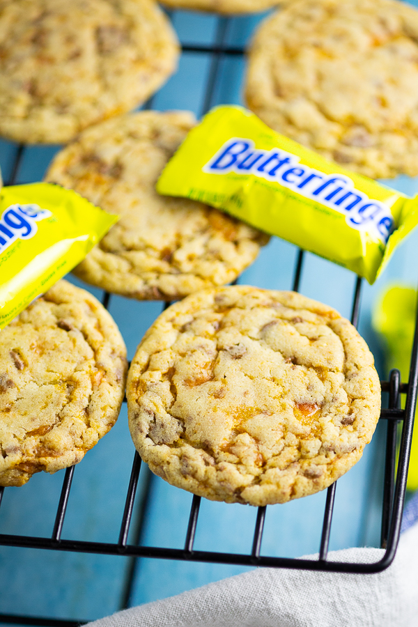 Butterfinger Cookies on a cooling rack with mini Butterfingers with an aqua wood background