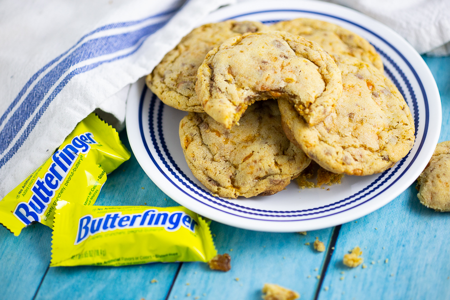 Butterfinger cookies stacked on a white plate next to mini Butterfingers and a white and blue linen on an aqua wood background