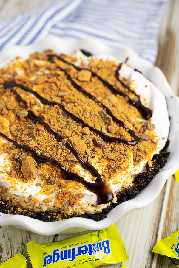 A whole Butterfinger pie in a white ruffled pie dish with Butterfingers and a white and blue linen around it.