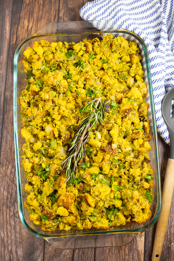 Cornbread dressing in a glass dish with a rosemary sprig on top on a rustic wood background