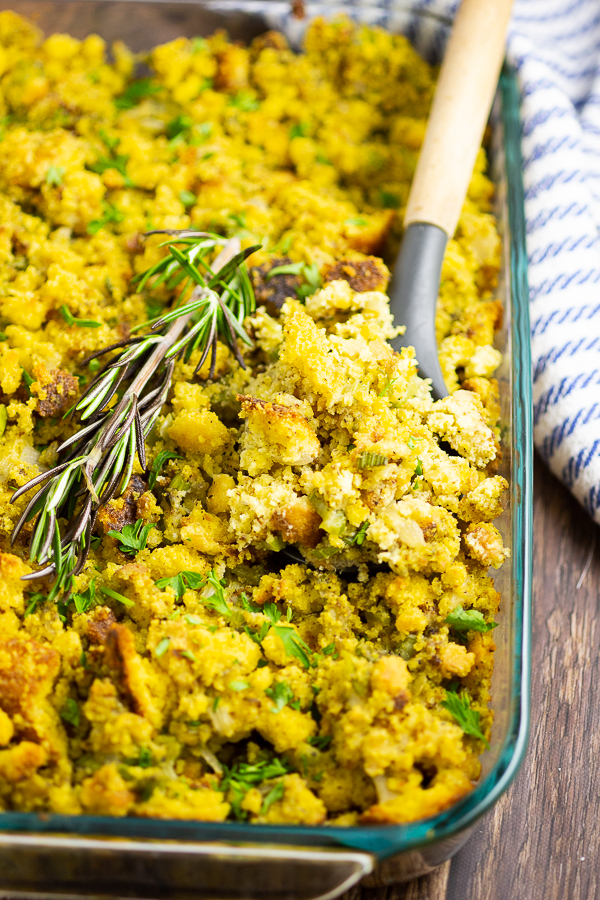 Cornbread dressing in a glass dish with a sprig of rosemary and a wooden spoon in the middle.