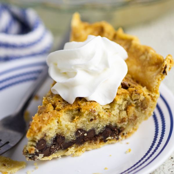 Slice of Kentucky Derby Pie topped with whipped cream on a small plate next to a fork