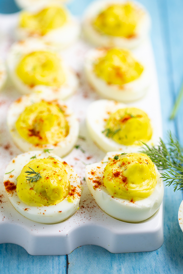 Deviled eggs on a white plate on a blue wood background with fresh dill