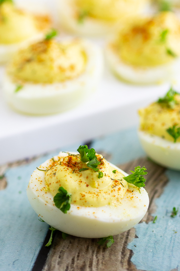 Deviled egg on a rustic wood background with more eggs behind it