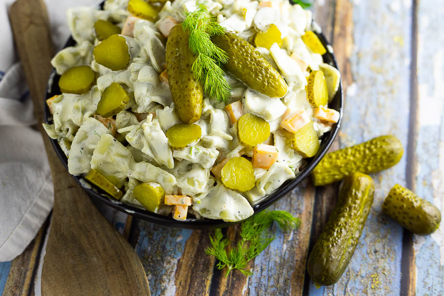Horizontal image of dill pickle pasta salad in a black bowl topped with 2 baby dills and a sprig of fresh dill. Bowl is placed on a rustic wood background with fresh herbs, 2 more baby dill pickles, and a wooden spoon