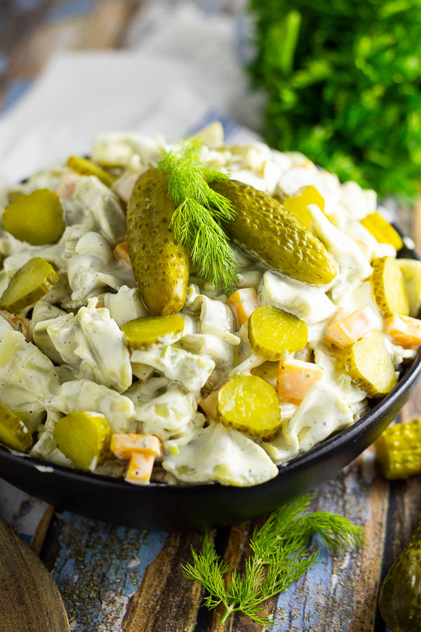 Dill pickle pasta salad in a black bowl topped with 2 baby dills and a sprig of fresh dill. Bowl is placed on a rustic wood background with fresh herbs and a wooden spoon