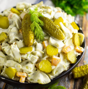 Square image of dill pickle pasta salad in a black bowl topped with 2 baby dills and a sprig of fresh dill. Bowl is placed on a rustic wood background with fresh herbs and a wooden spoon
