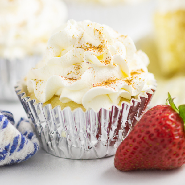 Tres Leches Cupcake topped with a sprinkle of cinnamon in a foil wrapper next to a fresh strawberry
