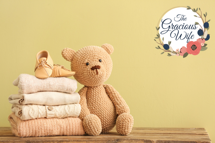 Baby clothes folded on a table with baby shoes on top next to a stuffed teddy bear