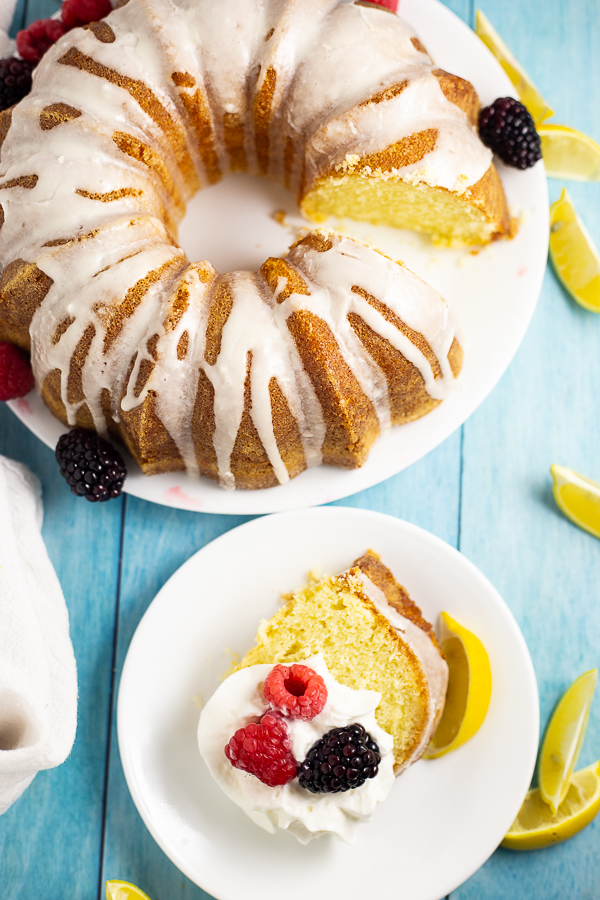 Overhead view of a lemon buttermilk pound cake with a slice cut out. The slice is on a separate plate topped with whipped cream, two raspberries, and a blackberry.