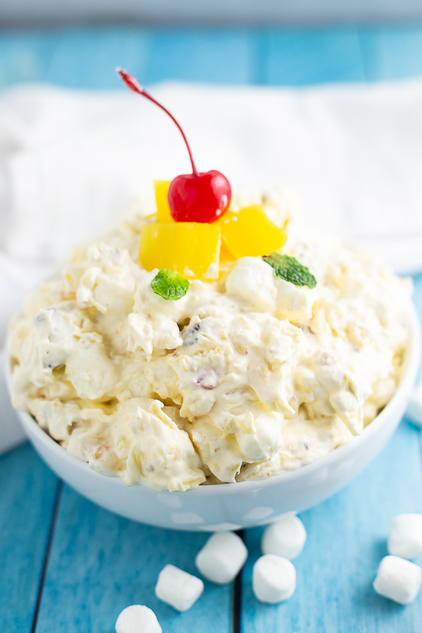 Side view of bowl of Pineapple Fluff topped with pineapple pieces and a cherry.
