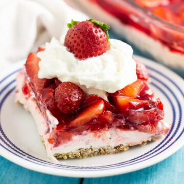 A slice of strawberry pretzel salad on a small plate topped with whipped cream and a fresh strawberry.