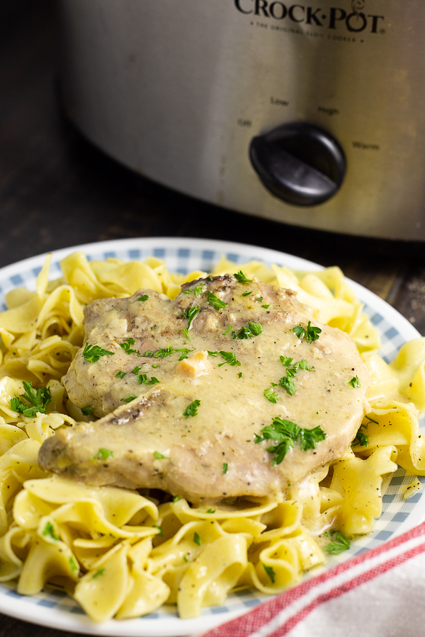 Side view of two Crock Pot Ranch Pork chops garnished with fresh parsley on a bed of buttery egg noodles in front of a slow cooker.