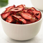 Bowl full of dried strawberries with strawberry leaves in the background