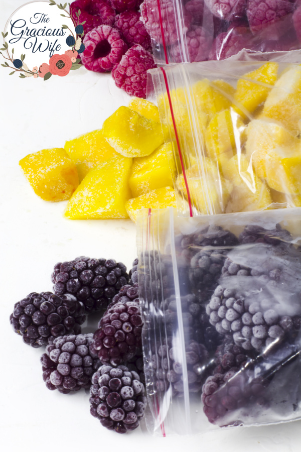 Frozen blackberries, mango, and raspberries in three separate plastic bags