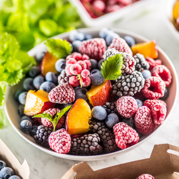 Bowl full of frozen raspberries, blackberries, blueberries, and peaches with mint leaves on top