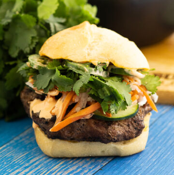 Front view of a banh mi burger piled high with toppings and spicy mayo