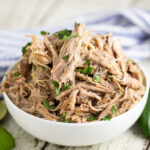 A bowl filled with slow cooker Chipotle carnitas, topped with chopped fresh cilantro