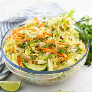 Large glass bowl filled with jicama slaw with a metal spoon taking a scoop out of it, surrounded by a lime wedge, a striped linen, and fresh cilantro
