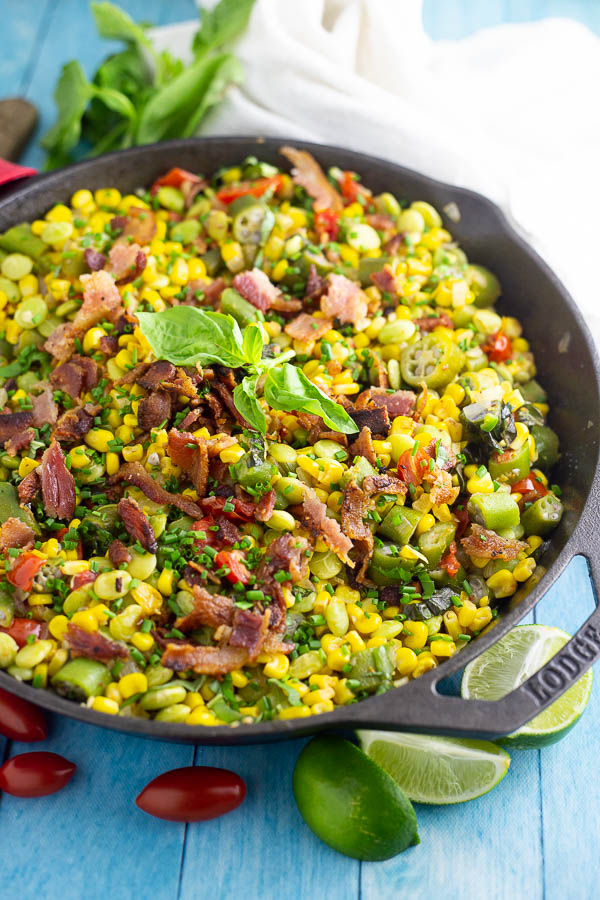 Southern succotash in a cast iron skillet topped with bacon and fresh basil