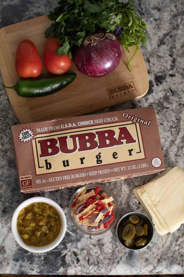 BUBBA burger package on a counter with tomatoes, jalapeno, onion, cilantro, green chiles, tortilla strips, and white American cheese.