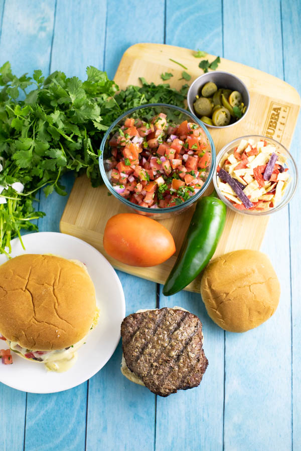Nacho burger ingredients spread out on a cutting board and a blue wood background