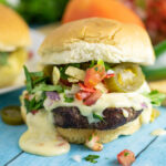 Close up of a nacho burger topped with queso, tortilla strips and jalapenos with fresh cilantro and another burger behind it.