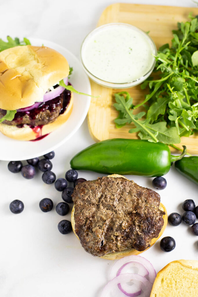 Ingredients to assemble spicy blueberry burgers including a burger on a bottom bun, red onion slices, blueberries, jalapeno, prepared jalapeno aioli, and arugula on a wooden cutting board