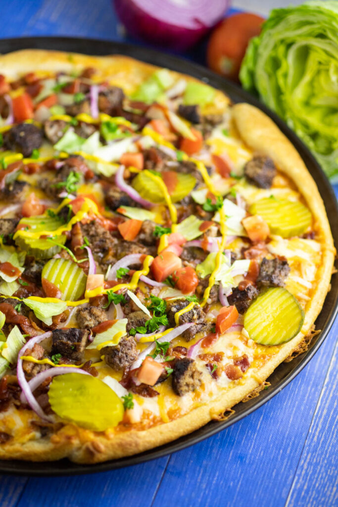 Close up side view of a bacon cheeseburger pizza on a blue wooden background with a wedge of iceberg lettuce, fresh tomato, and red onion in the background