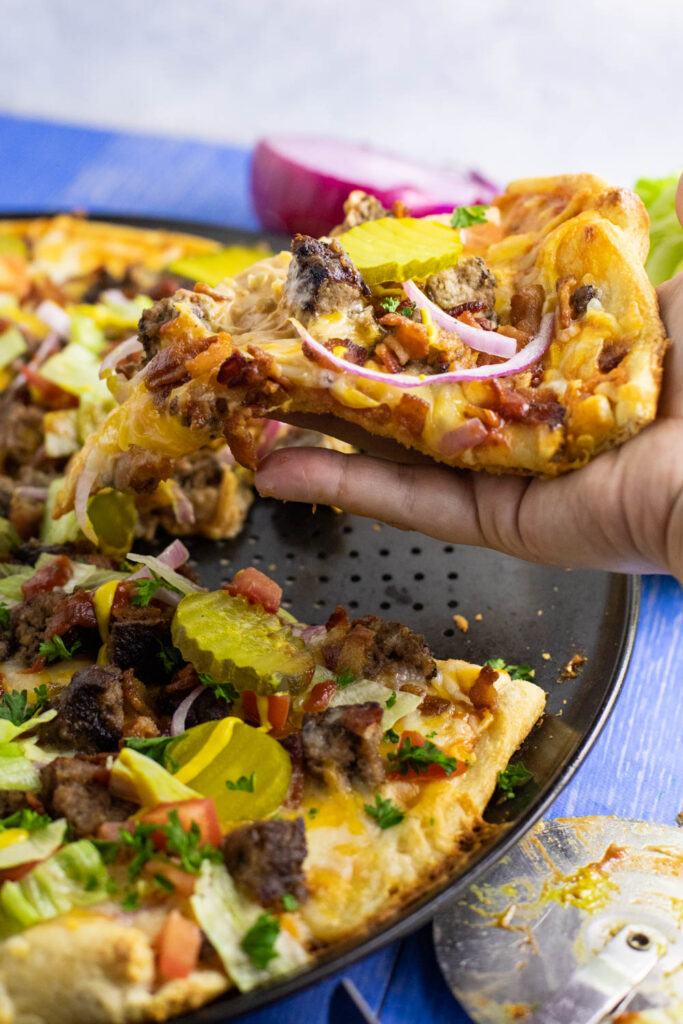 Hand pulling a slice of bacon cheeseburger pizza from the full pizza