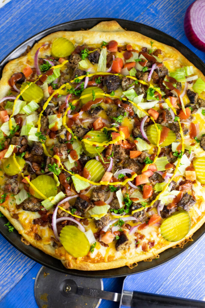Overhead view of a bacon cheeseburger pizza next to a pizza cutter and red onion on a blue wooden background.
